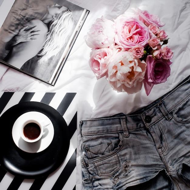 ショートパンツ、バラのブーケ、コーヒー、雑誌のフラットレイ Premium写真