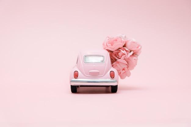 花の花束を提供するピンクのレトロなおもちゃの車 Premium写真