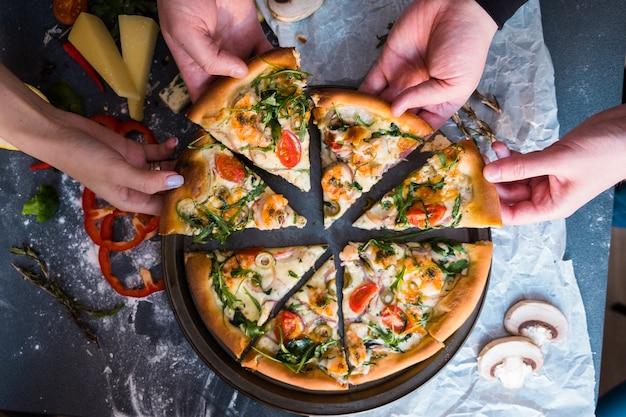 ピザを食べている友人。ピザのスライスをつかむ人の手 Premium写真