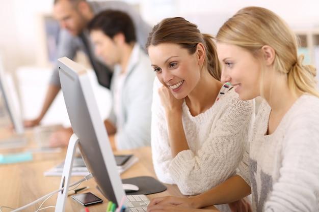 デスクトップの前で働く女子大生 Premium写真