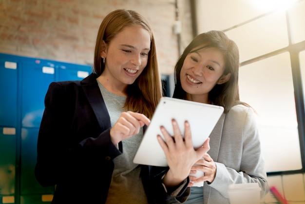 近代的なオフィスにプレゼンテーションのアイデアを議論する女性の同僚 Premium写真