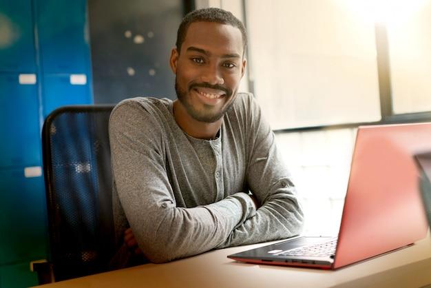 近代的なオフィススペースで働く若い黒人男性 Premium写真
