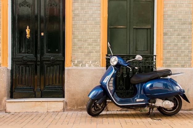スペインの町に駐車したビンテージベスパスクーターのビュー。 Premium写真