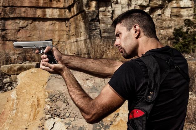 拳銃を指している威嚇するような男 Premium写真