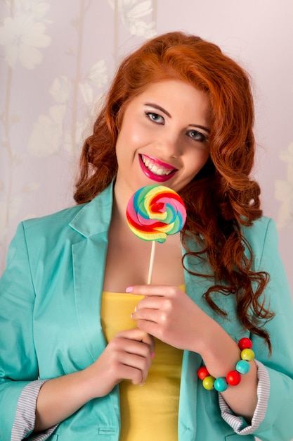 カラフルな服を着てロリポップキャンディーと美しい赤毛の女の子のビュー。 Premium写真