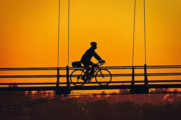 橋の上のシルエット自転車 Premium写真