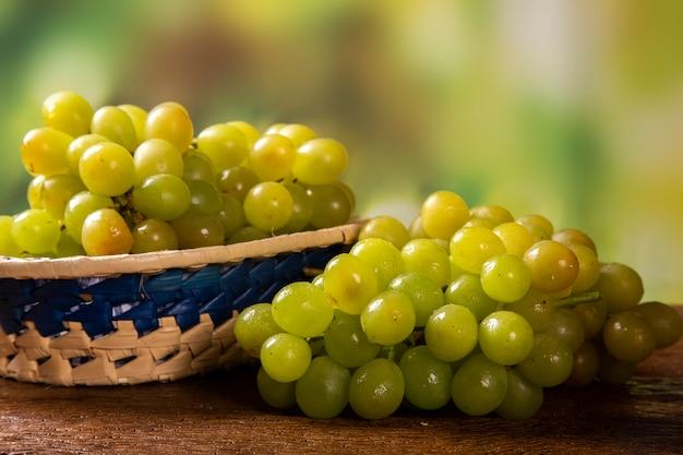 Гроздь зеленого винограда, плоды осени, символ изобилия на деревенском фоне дерева. Premium Фотографии