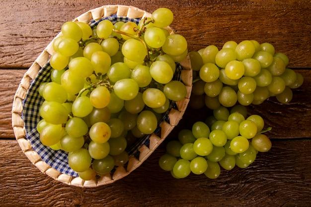 Гроздь зеленого винограда в корзине, плоды осени, символ изобилия на деревенском фоне дерева с копией пространства, вид сверху, крупным планом Premium Фотографии