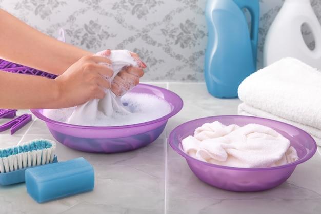 手の女性は石鹸水で手で服を洗います。 Premium写真