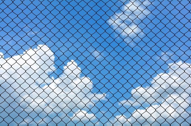 Клетка металлическая проволока на голубом небе с облаком летом - фон Premium Фотографии