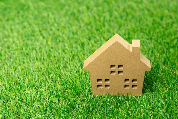 緑の芝生の上の家の小さなモデル。 Premium写真