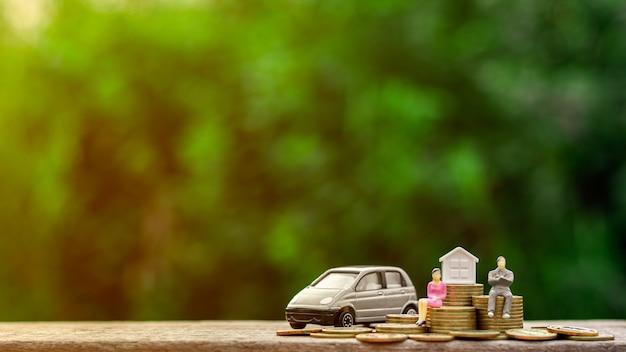 ミニチュア実業家図黄金のコインと車のモデルの上に座る。 Premium写真