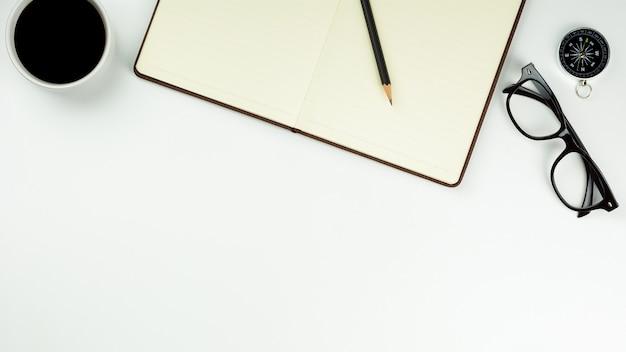 茶色の革ノートとコピースペースを持つ白い机の背景にコーヒーカップ。 - 事務用品や教育のコンセプト。 Premium写真