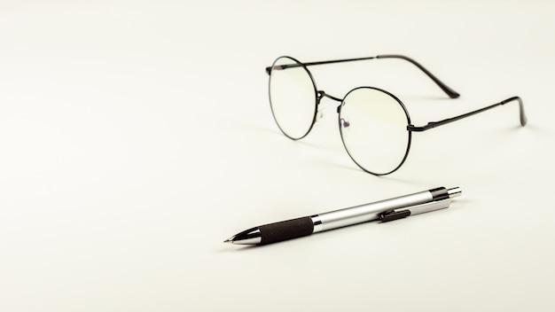 ペンと白い机の上の眼鏡。 Premium写真