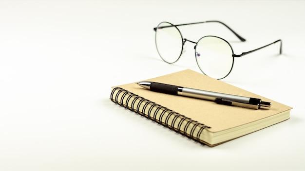 日記帳と白い机の背景にメガネのペン。 Premium写真