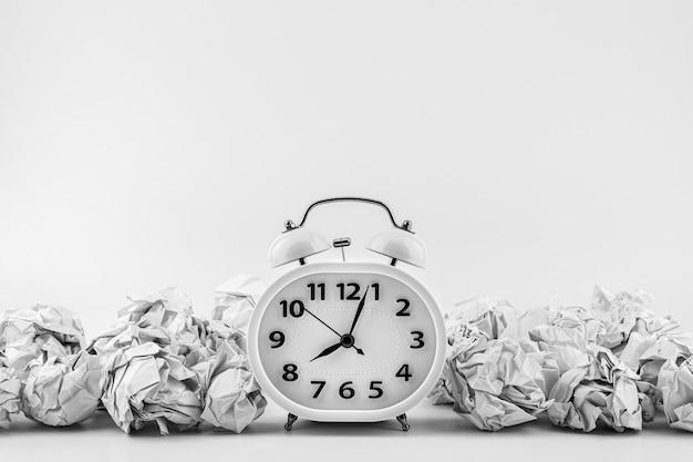しわくちゃの紙のボールの山の中の白い目覚まし時計。 - ビジネスタイムズのコンセプトです。 Premium写真