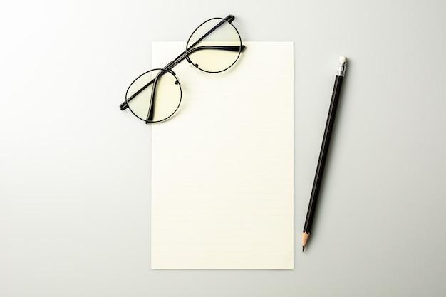 白紙のメモ用紙と灰色の机の上の鉛筆 Premium写真