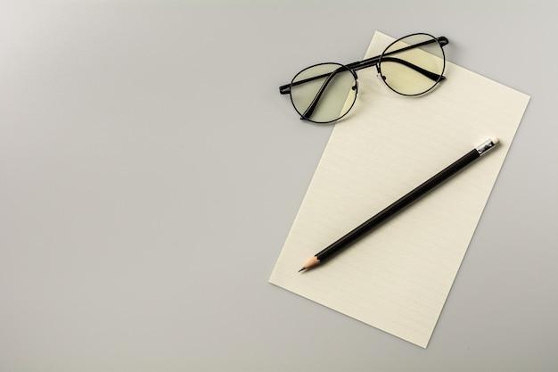 白紙のメモ用紙と灰色の机の背景に鉛筆 Premium写真