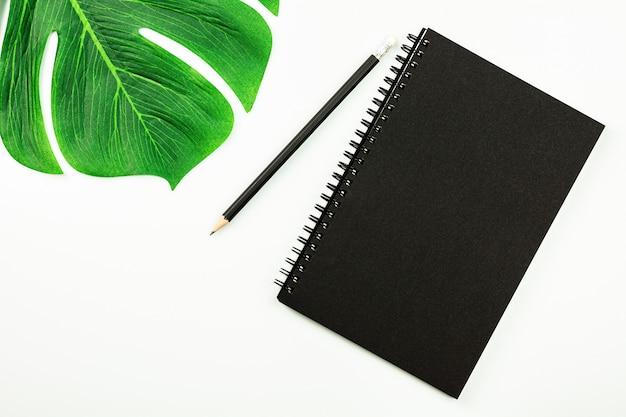 黒いノートとコピースペースを持つ白い机の上の鉛筆。 - 上面図。 Premium写真