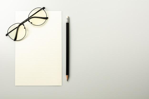 白紙のメモ用紙と灰色の机の背景に鉛筆。 Premium写真