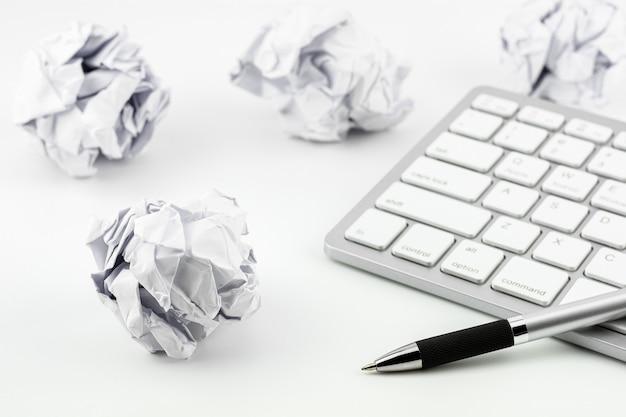 Ручки на клавиатуре компьютера и смятые бумажные шарики на белом столе Premium Фотографии