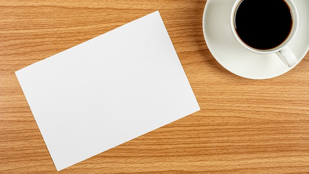 白紙のメモ用紙と木製の机の上のコーヒーカップ Premium写真