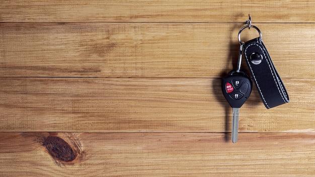 Ключ автомобиля с дистанционным управлением вися на деревянной стене. Premium Фотографии