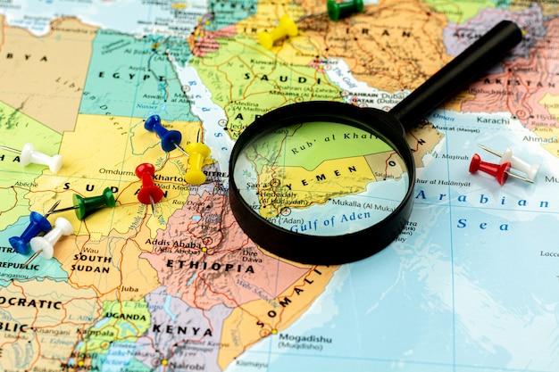 イエメンの世界地図セレクティブフォーカス上の虫眼鏡。経済とビジネス。 Premium写真