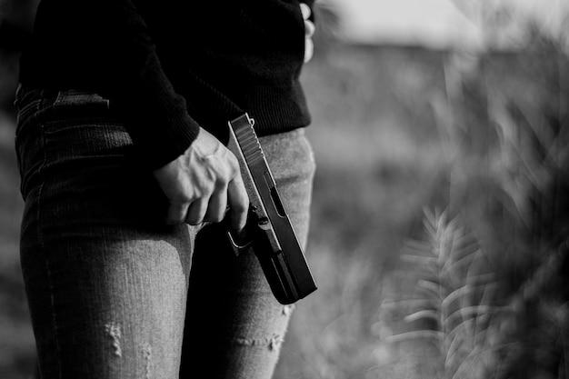 銃を手に持った女性。 -暴力と犯罪の概念。 Premium写真