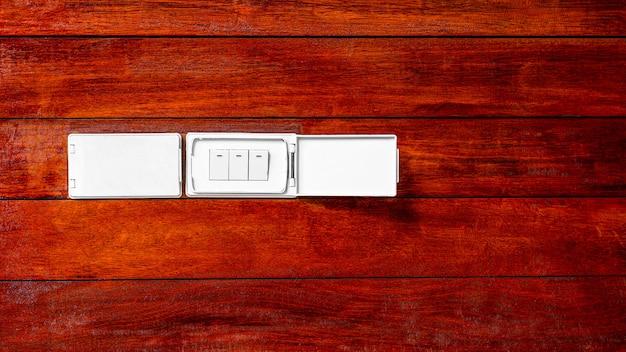 木製の壁にモダンなソケット電気スイッチ。 Premium写真