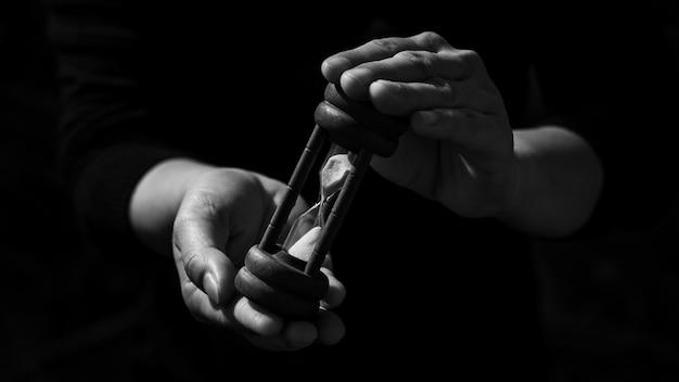 暗闇の中で古典的な木製砂時計を持ってビジネス男。思考と制御のタイミングアイデアコンセプト。 Premium写真