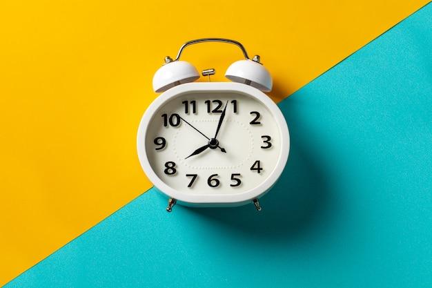 黄色と青の背景に白い目覚まし時計。 Premium写真