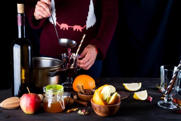 ホットホットワインを注ぐ女性の手 Premium写真