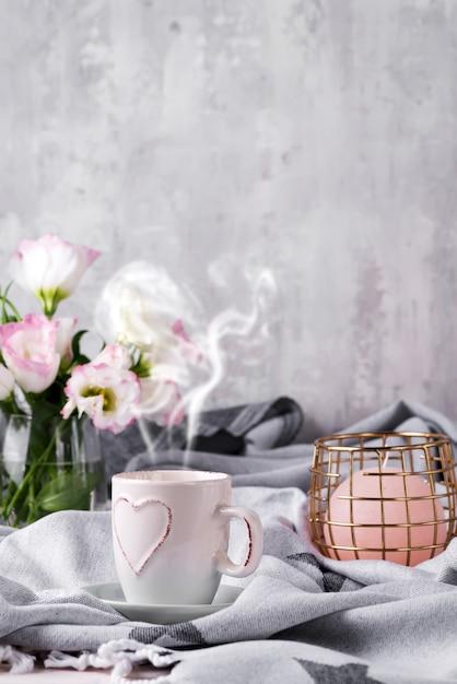 チョコレート、花トルコギキョウ、キャンドル、ベッドで毛布の上にコーヒーのカップを持っています。 Premium写真