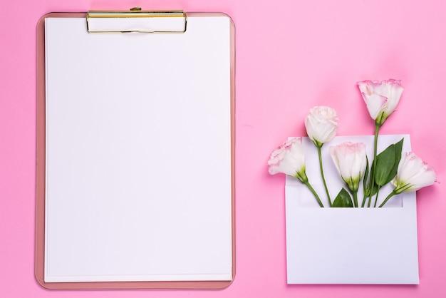 Минимальная композиция с эустомой цветы в конверте с буфером обмена на розовом фоне, вид сверху. день святого валентина, день рождения, мама или свадебные открытки Premium Фотографии