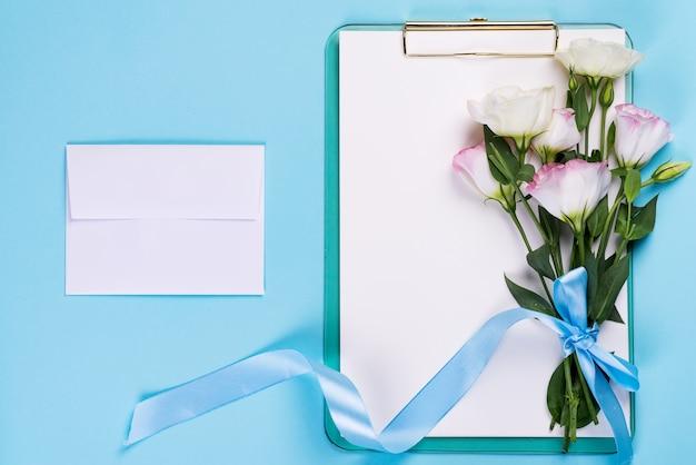 Минимальная композиция с эустомой цветы в конверте с буфером обмена на синем фоне, вид сверху. день святого валентина, день рождения, мама или свадебные открытки Premium Фотографии