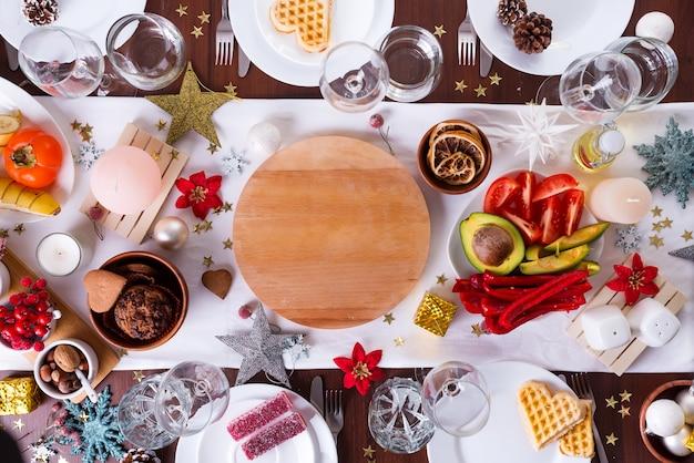 Рождественская сервировка с едой на тарелку и украшения на темный деревянный стол, плоская планировка Premium Фотографии