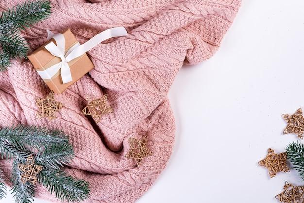 ピンクのニットセーターギフトボックス、クリスマスの装飾、モミの枝、トップビュー。クリスマスの静物 Premium写真