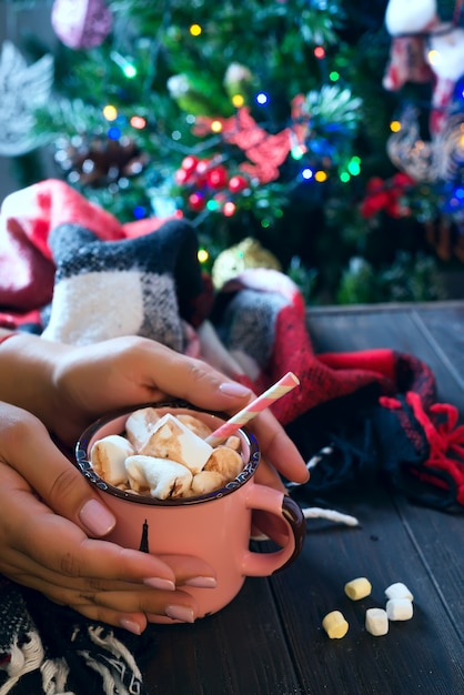 クリスマスツリーの上の木製のテーブルにマシュマロとココアやチョコレートのカップを持っている女性の手 Premium写真