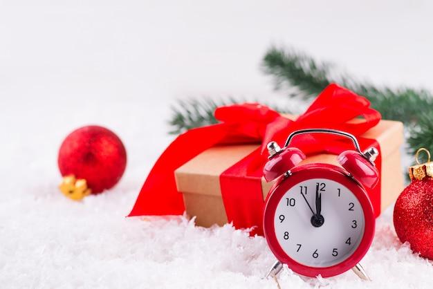 赤いボールと赤い古い時計、新鮮な雪の中で大きな赤い弓立って茶色のギフトボックス Premium写真
