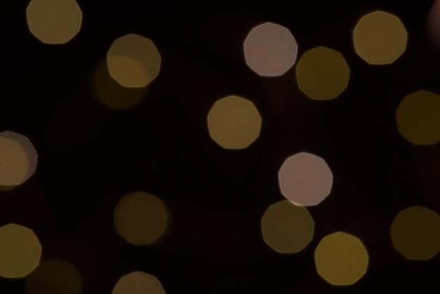 Желтый блеск текстуры боке на черном Premium Фотографии