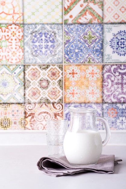 ガラスの水差しとガラス、古い色のキッチンタイルと壁の新鮮な牛乳 Premium写真