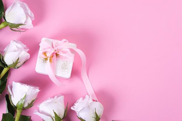 ピンクの背景にピンクのリボンとピンクのバラと白のギフトボックス Premium写真