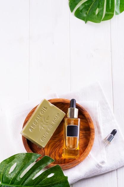 血清またはヒアルロン酸と木製プレート、ヤシの葉、白いタオルの上にオリーブ石鹸の化粧品ボトル Premium写真