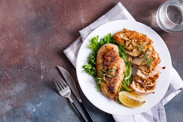 鶏胸肉のグリル、サラダと全体とレモンのスライス。古ダイエット。 Premium写真