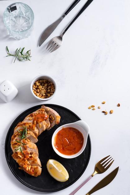 鶏胸肉のグリル、ソース、ピーナッツ、レモンのプレート Premium写真