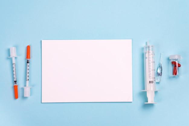 注射器、錠剤、コピースペース付きの紙 Premium写真