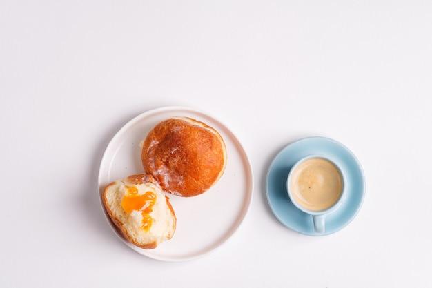 白いセラミックプレートとライトグレーのコーヒーカップに自家製焼きドーナツ。フラット横たわっていた。 Premium写真