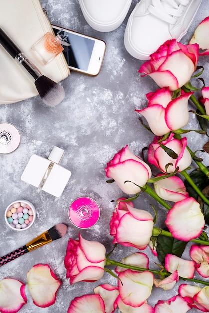 香水、電話、灰色の背景にスニーカーで化粧品とバラの花束 Premium写真