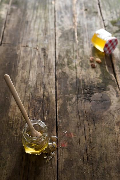 Мед органический в банке с деревянной палочкой на старом деревянном фоне, чистый натуральный сладкий Premium Фотографии